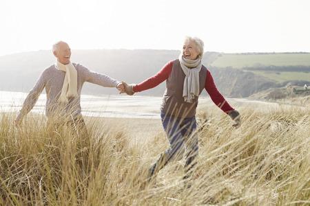 冬のビーチで砂丘を歩いて年配のカップル 写真素材