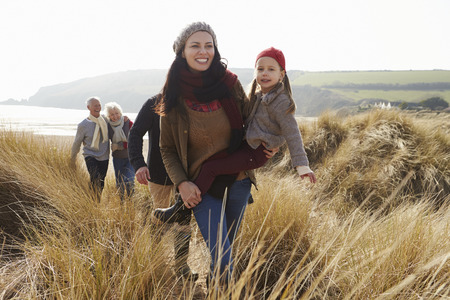 winter woman: Multi Generation Family In Sand Dunes On Winter Beach Stock Photo