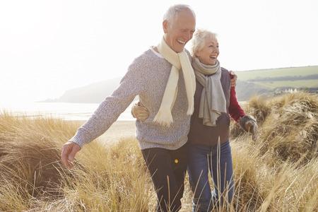 caminando: Pares mayores que recorren a trav�s de las dunas de arena en la playa del invierno