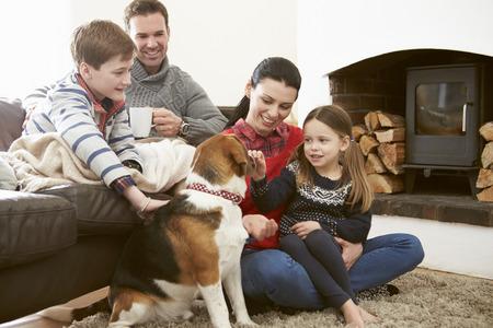 Rodina relaxační v interiéru i hlazení psa