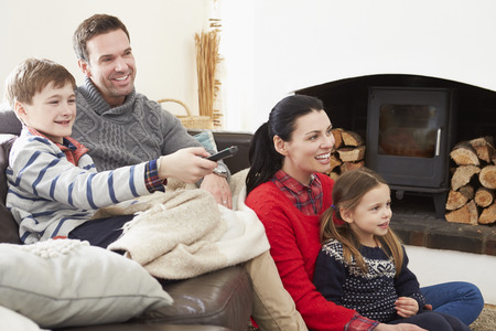 winter woman: Family Relaxing Indoors Watching Television Together Stock Photo
