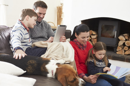 Family Relaxing Reading Book And Using Digital Tablet photo