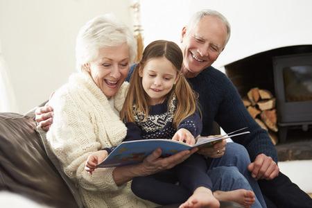 함께 가정에서 조부모와 손녀 책을 읽고