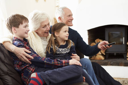 Grandparents Sitting On Sofa Watching TV With Grandchildren photo
