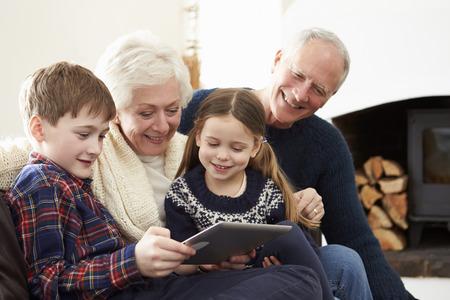 abuelos: Abuelos que usa la tableta digital en el sof� con los nietos Foto de archivo