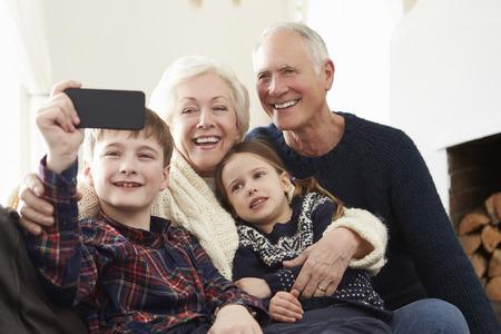 abuelos: Abuelos y nietos que se sientan en el sof� Tomando Autofoto Foto de archivo