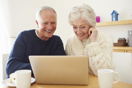 dos personas platicando: Pares mayores usando la computadora port�til a la tienda online