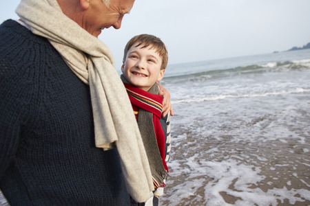 Grandfather And Grandson Walking On Winter Beach photo