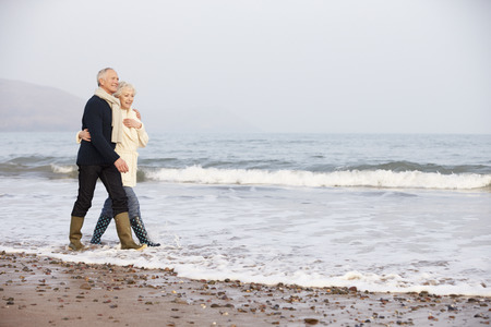 冬の浜辺に沿って歩いて年配のカップル