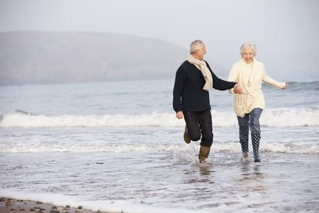 gente corriendo: Pareja mayor ejecuta a lo largo de la playa de invierno