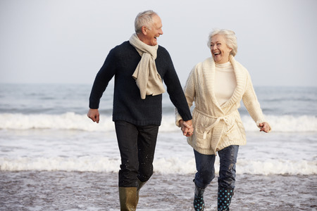 ancianos caminando: Pareja mayor ejecuta a lo largo de la playa de invierno