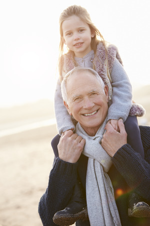 Grandfather And Granddaughter Walking On Winter Beach photo