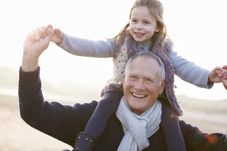 hombre viejo: Abuelo y nieta recorre en la playa de invierno