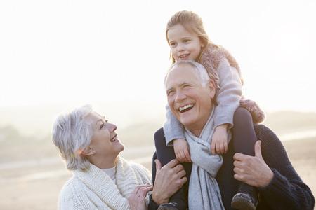 Les grands-parents et sa petite fille marchant sur la plage d'hiver Banque d'images - 33525314