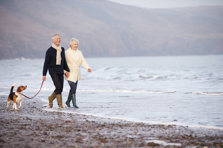 person walking: Senior Couple Walking Along Winter Beach With Pet Dog