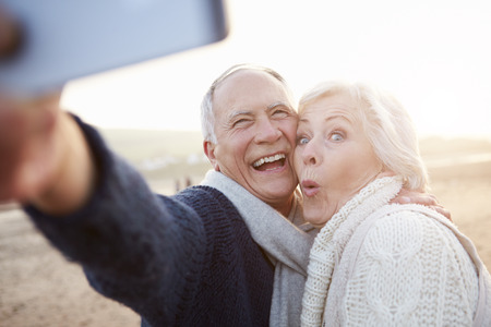 an elderly person: Senior pareja de pie en la playa Tomando Autofoto