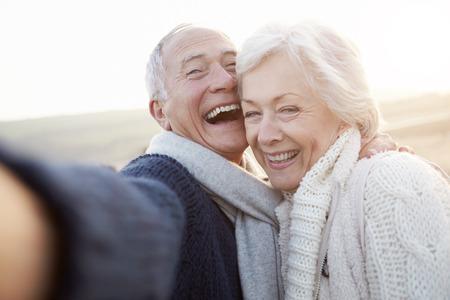 femmes souriantes: Couple senior debout sur la plage Prendre Selfie Banque d'images
