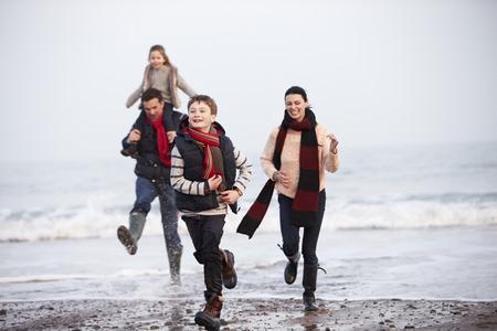 scarf beach: Familia que se ejecuta en la playa del invierno