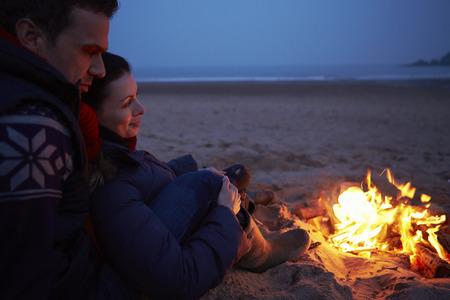 Paar zitten door de brand op Winter strand