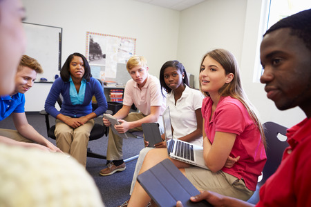 teens school: High School Students Taking Part In Group Discussion Stock Photo