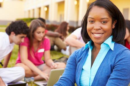 high school teacher: High School Teacher Sitting Outdoors With Students On Campus