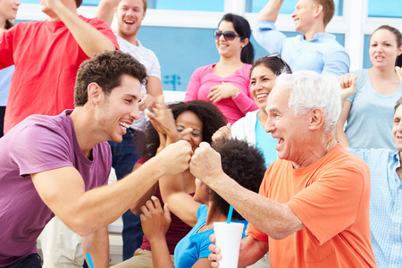 person: Spectators Cheering At Outdoor Sports Event Stock Photo
