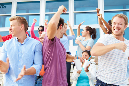 sports fans: Spectators Cheering At Outdoor Sports Event Stock Photo