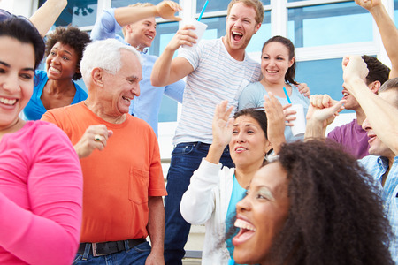 male age 40's: Spectators Cheering At Outdoor Sports Event Stock Photo