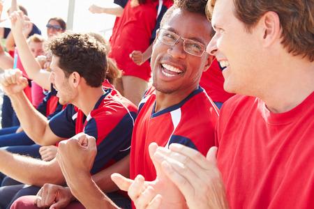 aplaudiendo: Espectadores en Colores del equipo de observación de eventos Deportes Foto de archivo