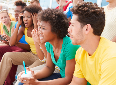 sports venue: Disappointed Spectators In Team Colors Watching Sports Event