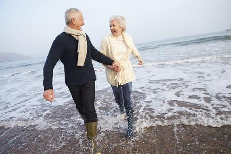 jubilados: Pares mayores que recorren a lo largo de la playa de invierno Foto de archivo