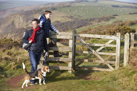 Father And Son With Dog Walking Along Coastal Path photo