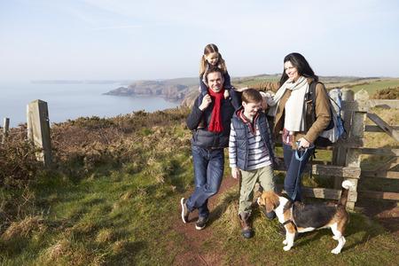 海岸のパスに沿って歩く犬連れのご家族
