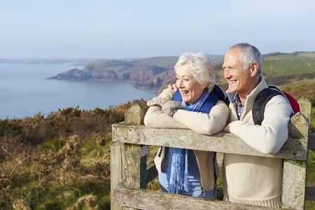 retirement happy man: Senior Couple Walking Along Coastal Path