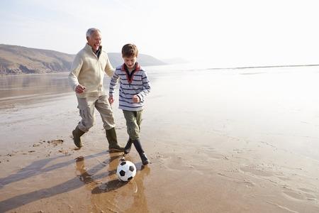 祖父と孫の冬のビーチでサッカーをプレイ