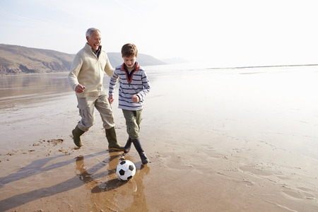 two person: Grandfather And Grandson Playing Football On Winter Beach