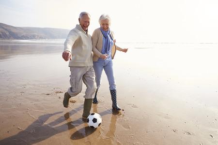 jugando al futbol: Senior pareja jugando al f�tbol en la playa de invierno Foto de archivo