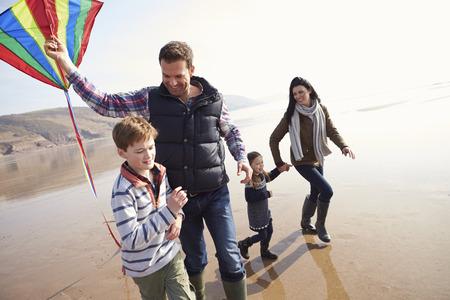 Familie die langs het Strand van de Winter Flying Kite Stockfoto