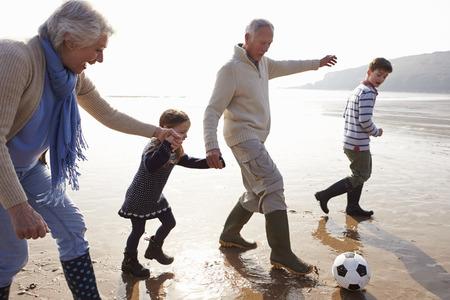 Abuelos con nietos jugando al fútbol en la playa Foto de archivo