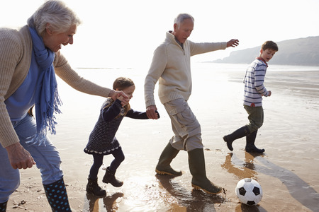 Grandparents With Grandchildren Playing Football On Beach Stockfoto