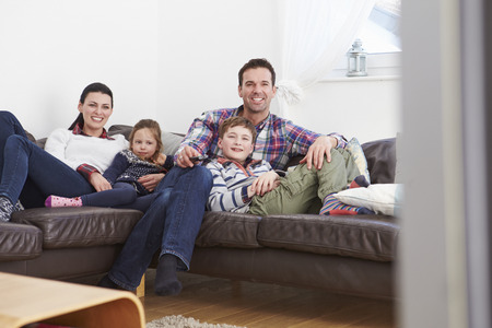 man watching tv: Family Relaxing Indoors Watching Television Together Stock Photo