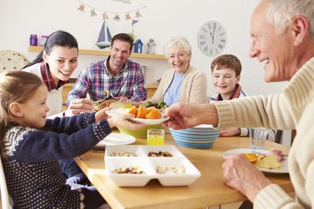 lunch: Multi generacional come el almuerzo en la tabla de cocina