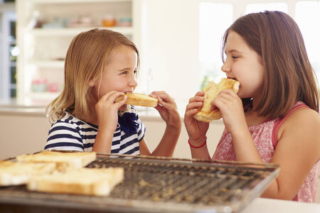 comiendo pan: Dos Muchachas que comen el queso en tostadas en la cocina