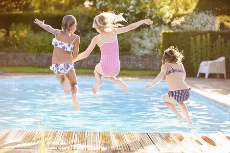 jumping: Grupo de muchachas Salto En Piscina al aire libre