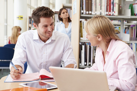 sitt: Teacher Helping Mature Student With Studies In Library