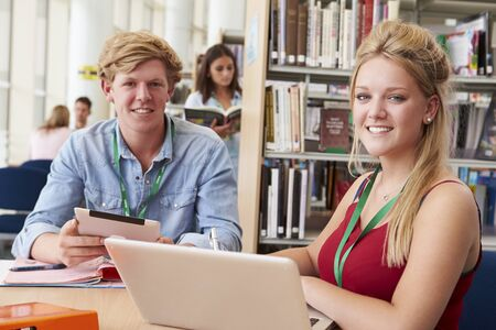 Two College Students Studying In Library Together