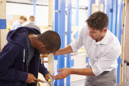 Teacher With Student In Carpentry Class Fitting Door Lock Stock Photo