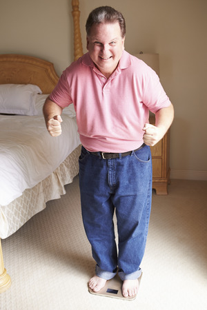 overweight man: Happy Overweight Man Standing On Scales In Bedroom Stock Photo
