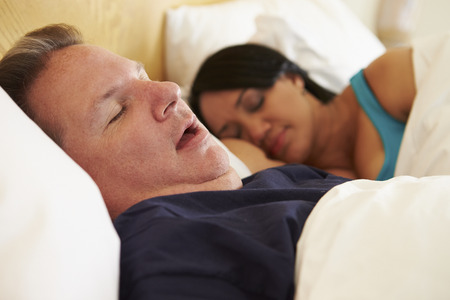Couple Asleep In Bed With Man Snoring photo