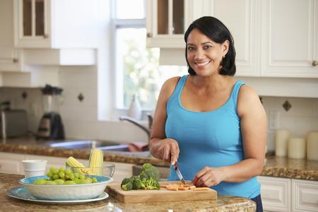 과 체중 여자 주방에서 야채를 준비 스톡 콘텐츠
